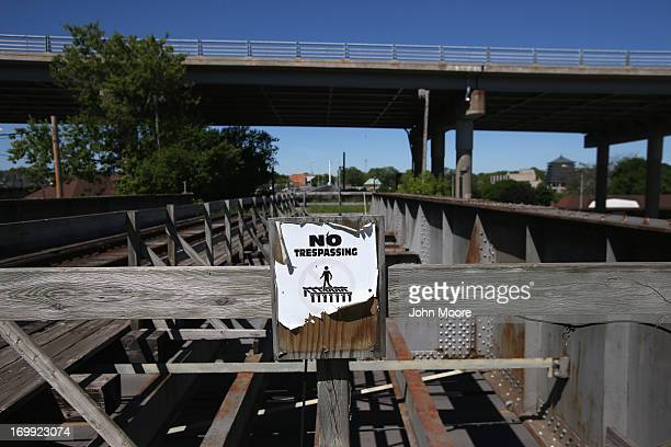 A sign urges pedestrians not to walk over a rail bridge connecting the US with Canada on June 4 2013 near Black Rock New York US Border Patrol agents...