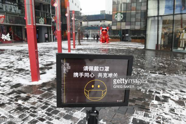 A sign urges visitors to wear face masks at the entrance to an empty shopping mall in Beijing on February 5 2020 China's struggle to contain the...