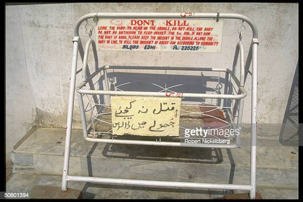 Sign urging not to kill unwanted baby posted on bassinet at charitable Edhi Foundation home for for runaway & abandoned children.
