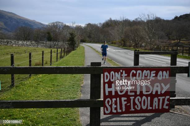 Sign urging visitors to stay at home and not go on holiday is seen in Llanberis in Snowdonia, north Wales on April 5, 2020 as the warm weather tests...