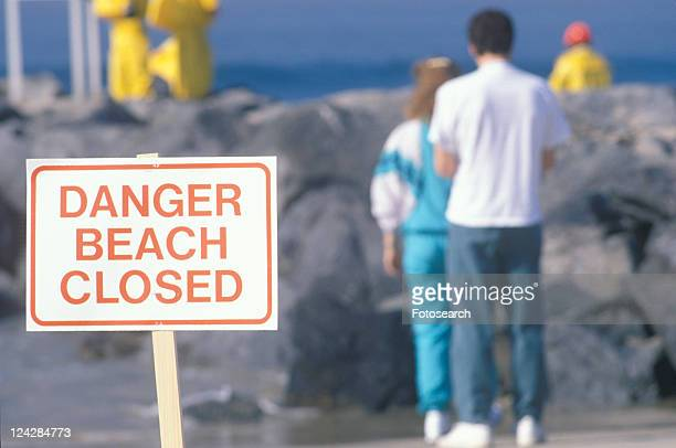 A sign warning, dangerûbeach closed with people in the background