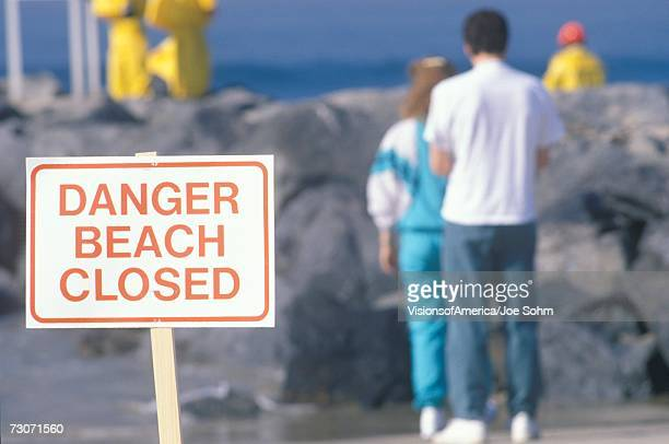 'A sign warning, danger?beach closed with people in the background'