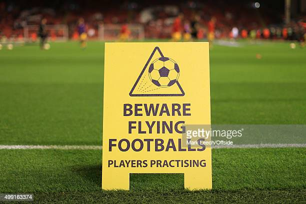A sign warning fans to beware of flying footballs as there are players practising before the UEFA Europa League Group B match between Liverpool and...