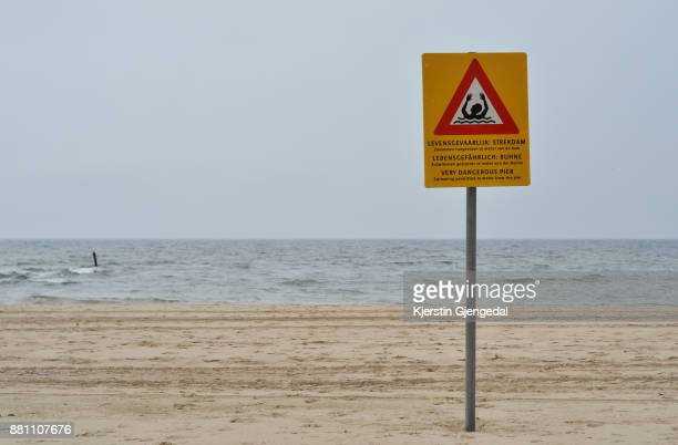A sign warning of a submerged pier on a beach by the North Sea