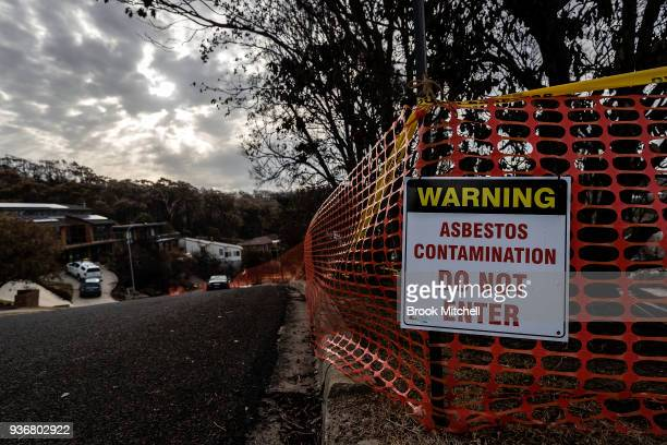 A sign warning of asbestos contamination is seen on a Tathra street on March 23 2018 in Tathra Australia A bushfire which started on 18 March...