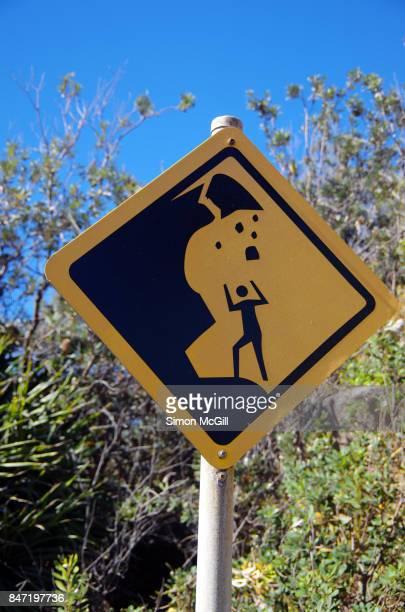 Sign warning of cliff rockfalls at Front Beach, Arakoon National Park, New South Wales, Australia