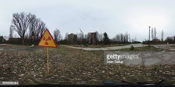 A sign warning of radiation contamination stands near former apartment buildings on April 9 2016 in Pripyat Ukraine Pripyat built in the 1970s as a...