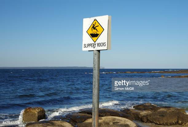 Sign warning of slippery rocks at Jervis Bay, New South Wales, Australia