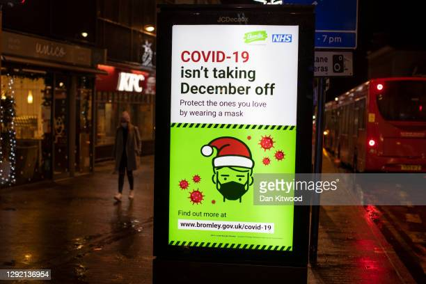 Sign warning shoppers about the risks ov Covid-19 as consumers do their last minute Christmas shopping in Bromley, as new 'Tier 4' rules come into...