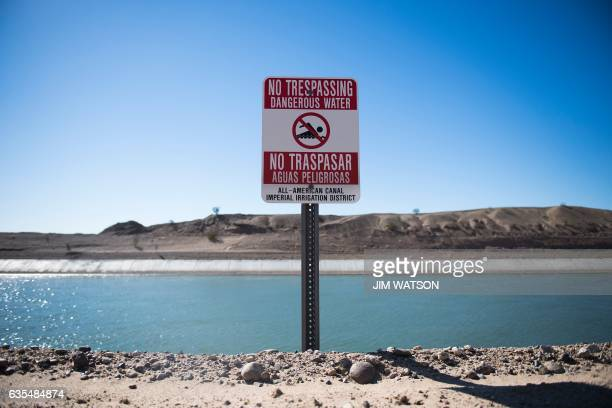 A sign warns against swimming the All American Canal near the border fence on the US/Mexico border in Winterhaven CA on February 15 2017 this image...