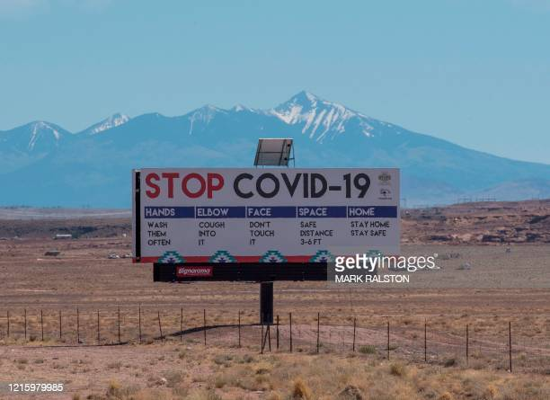 Sign warns against the Covid-19 virus near the Navajo Indian nation town of Tuba City, Arizona on May 24, 2020. - According to the Centers for...
