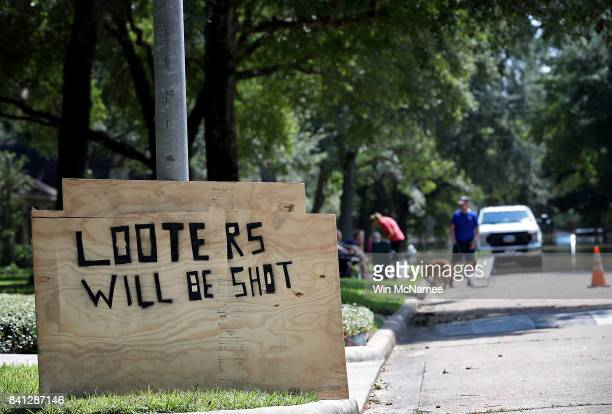 A sign warns looters in front of a home near the Barker Reservoir August 31 2017 in Houston Texas The neighborhoods surrounding the reservoir are...