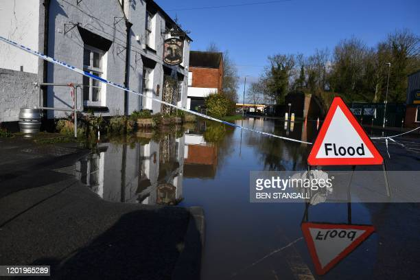 TOPSHOT A sign warns of flooding in Tewkesbury Gloucestershire western England on February 20 as heavy rain threatens further flooding in Britain...