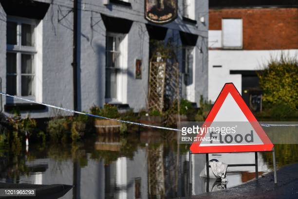 Sign warns of flooding in Tewkesbury, Gloucestershire, western England on February 20 as heavy rain threatens further flooding in Britain. -...