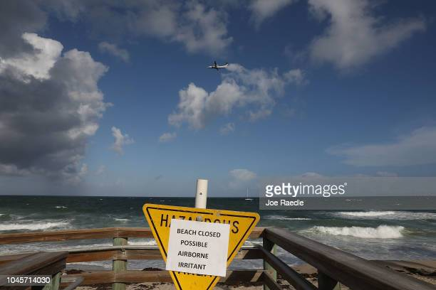 A sign warns of possible airborne irritants as Palm Beach County officials announced that all county beaches are closed due to red tide affecting...
