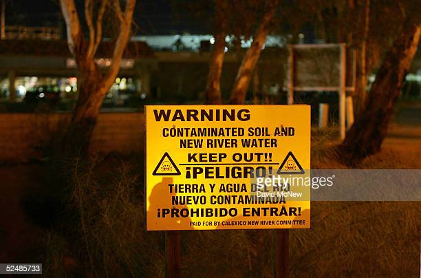 A sign warns of the danger of entering the New River reportedly the most polluted river in the US and down which some illegal immigrants float across...