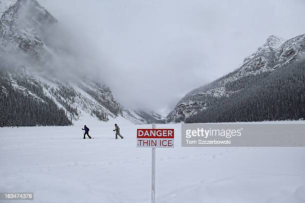 A sign warns of thin ice as a couple of crosscountry skiers pass through during an outdoor shinny hockey tournament at the 4th Annual Lake Louise...