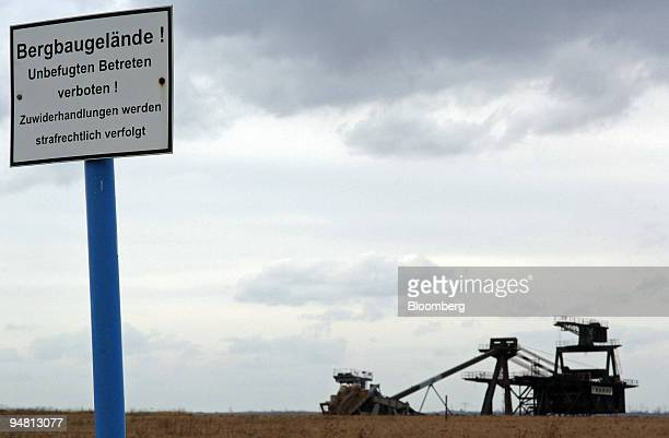 A sign warns trespassers to stay off the site where a bucketwheel excavator prepares land for lignite mining at the edge of the medieval village...