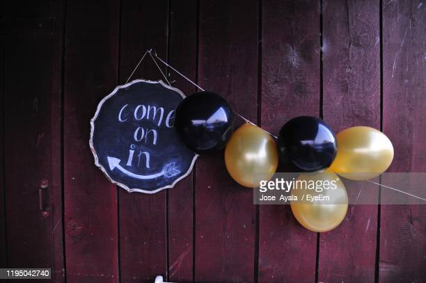 sign with balloons hanging on wooden wall - jose ayala stock pictures, royalty-free photos & images