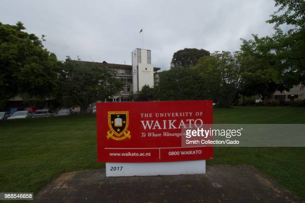 Sign with campus buildings in background at the University of Waikato in Hamilton, New Zealand on an overcast day, November, 2017.