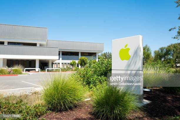 Sign with green colored logo amid landscaping, with facades of buildings in background, near the headquarters of Apple Computers in the Silicon...