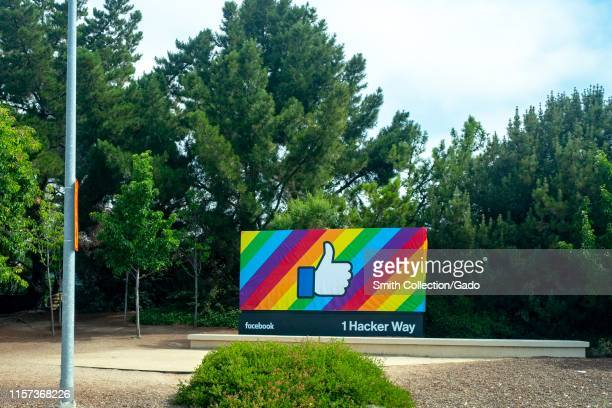 Sign with logo at entrance to headquarters of Facebook Inc at 1 Hacker Way in Menlo Park, California, decorated with a rainbow flag design in...