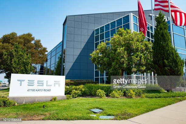 Sign with logo for Tesla Motors in front of new glass building near the company's headquarters in the Silicon Valley Fremont California July 28 2018
