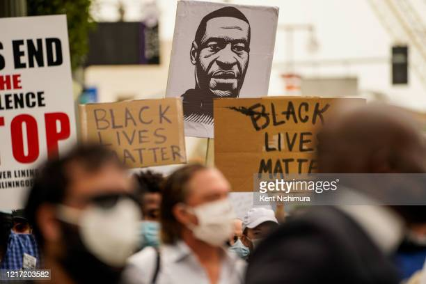 A sign with the likeness of George Floyd is seen as Protesters and Clergy members from the Los Angeles area participate in a march and peaceful...