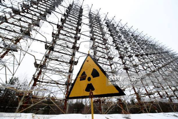 A sign with the radiation warning symbol is seen in front of the construction of the 'Duga' Soviet overthehorizon radar system near Chernobyl on...