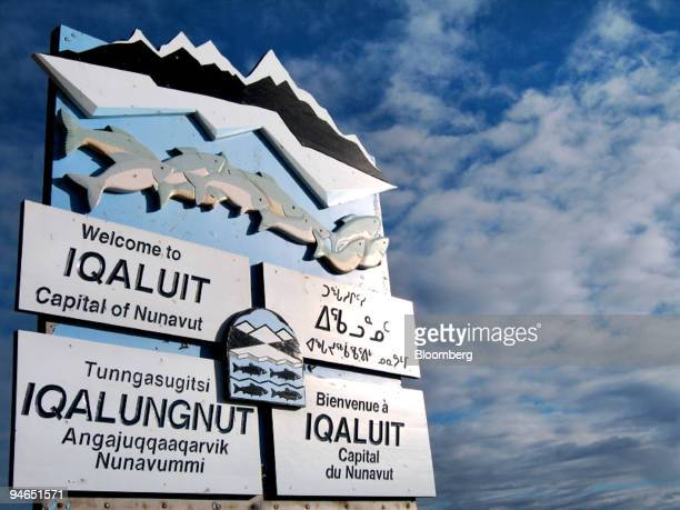 A sign written in various languages clockwise from top left English Inuktitut French and Inuktikut welcomes visitors to Iqaluit Nunavut Canada on Aug...