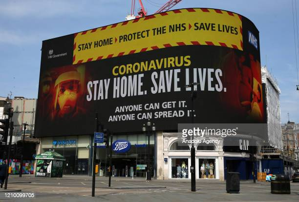 "Signage about coronavirus advice people to âStay home. Save lives"" is displayed on the advertising boards at Piccadilly Circus in London United..."