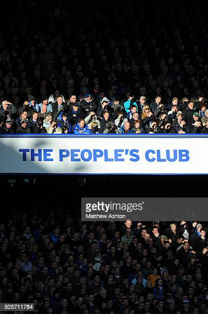 Signage at Everton Football Club at Goodison Park stadium as fans shield the sun from their eyes saying THE PEOPLE'S CLUB