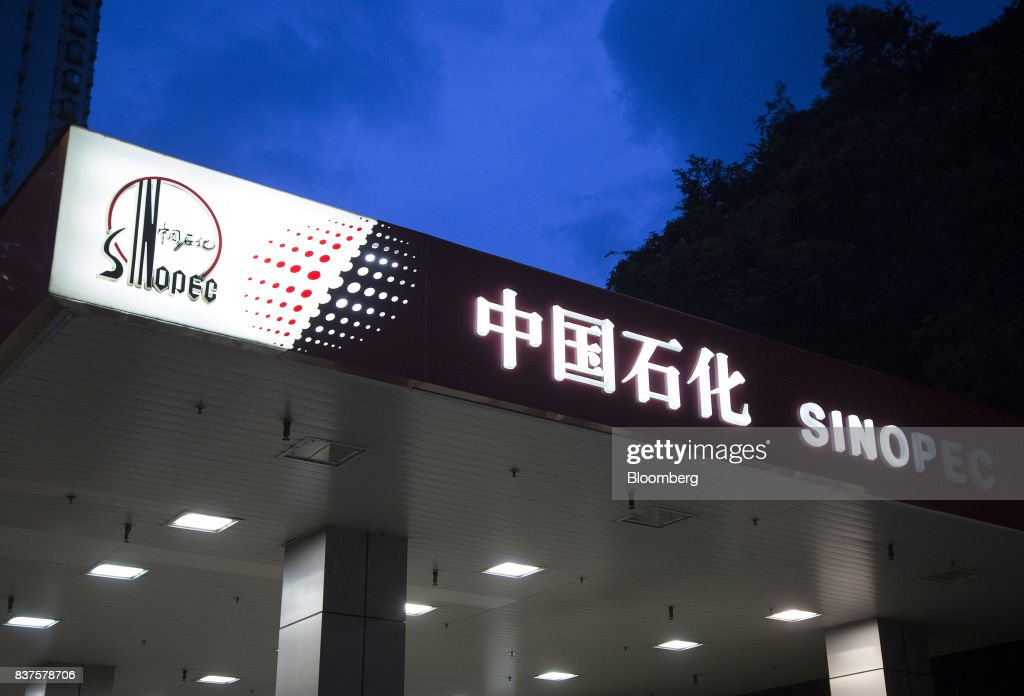 Signage atop a China Petroleum & Chemical Corp. (Sinopec) gas station stands lluminated at dusk in Hong Kong, China, on Tuesday, Aug. 22, 2017. Sinopec is scheduled to report second-quarter results on Aug. 25. Photographer: Vivek Prakash/Bloomberg via Getty Images