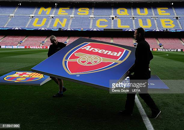 UEFA signage crew remove the Arsenal crest after a rehersal ahead of the UEFA Champions League Round of 16 second leg match between FC Barcelona and...