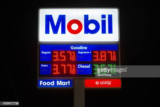 Signage displays fuel prices at an Exxon Mobil Corp gas station at night in Seattle Washington US on Tuesday July 24 2018 Exxon Mobil Corp is...