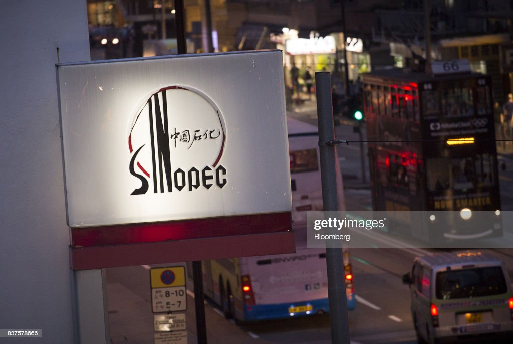 Signage for a China Petroleum & Chemical Corp. (Sinopec) gas station stands next to a road at dusk in Hong Kong, China, on Tuesday, Aug. 22, 2017. Sinopec is scheduled to report second-quarter results on Aug. 25. Photographer: Vivek Prakash/Bloomberg via Getty Images