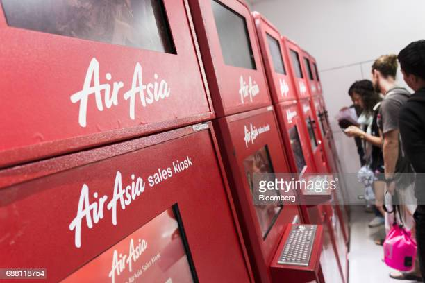 Signage for AirAsia Bhd are displayed on the company's automated sales kiosks at Kuala Lumpur International Airport 2 in Sepang Selangor Malaysia on...