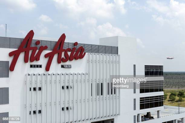 Signage for AirAsia Bhd is displayed atop the company's headquarters building as an AirAsia aircraft approaches to land at Kuala Lumpur International...