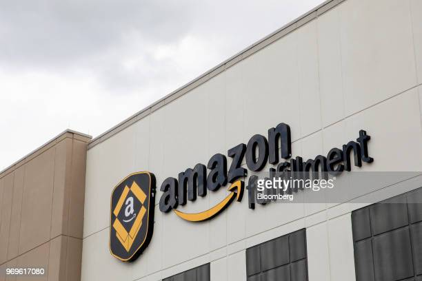 Signage for Amazoncom Inc is displayed atop the company's fulfillment center in Robbinsville New Jersey US on Thursday June 7 2018 Seattlebased...