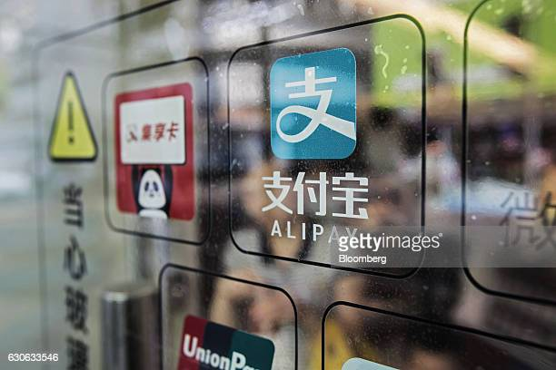 Signage for Ant Financial Services Group's Alipay payment system an affiliate of Alibaba Group Holding Ltd is displayed on a store entrance in...