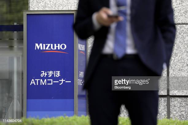 Signage for automated teller machines at a Mizuho Bank Ltd., a unit of Mizuho Financial Group Inc. , is displayed outside a branch in Tokyo, Japan,...