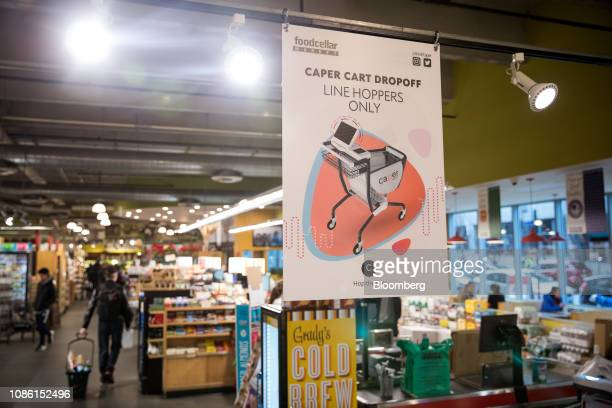 Signage for Caper Inc smart shopping carts hangs on display at a Foodcellar Co grocery store in the Long Island City neighborhood in the Queens...