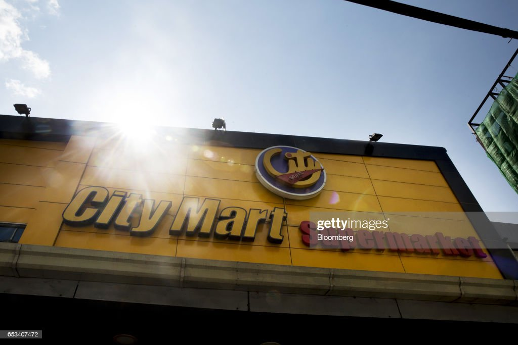 Signage for City Mart Supermarket, operated by City Mart Holdings Co., is displayed atop a store in Yangon, Myanmar, on Saturday, March 11, 2017. City Mart has 20 years of market knowledge to help it compete against international players, said Win Win Tint, managing director of City Mart in a Bloomberg interview on March 9. Photographer: Brent Lewin/Bloomberg via Getty Images