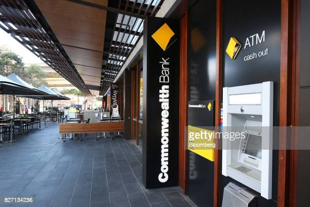 Signage for Commonwealth Bank of Australia is displayed next to an automated teller machine outside a branch in Sydney Australia on Monday Aug 7 2017...