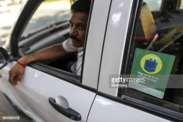 Signage for digital payment service Ola Money operated by ANI Technologies Pvt is displayed on the window of a taxi in Bengaluru India on Saturday...