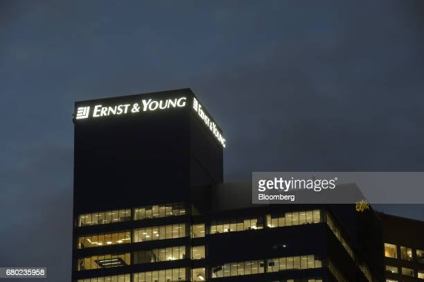 Signage for Ernst Young LLP is illuminated atop the company's building in Melbourne Australia on Friday April 28 2017 Australia has some of the...