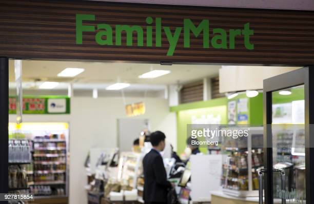 Signage for FamilyMart UNY Holdings Co's FamilyMart convenience stores is displayed atop a store entrance in Tokyo Japan on Friday Feb 23 2018...