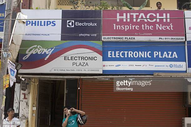 Signage for Godrej Group, Philips AB, Electrolux AB and Hitachi Ltd is seen outside an electronics store as a customer talks on a mobile phone in New...