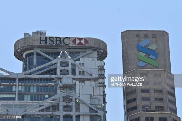 Signage for HSBC and the Standard Chartered Bank are displayed on the local headquarters of each bank in Hong Kong on April 28 2020 HSBC on April 28...