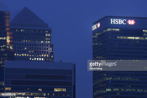 Signage for HSBC Holdings Plc sits illuminated atop the company headquarters in the Canary Wharf business financial and shopping district at dawn in...